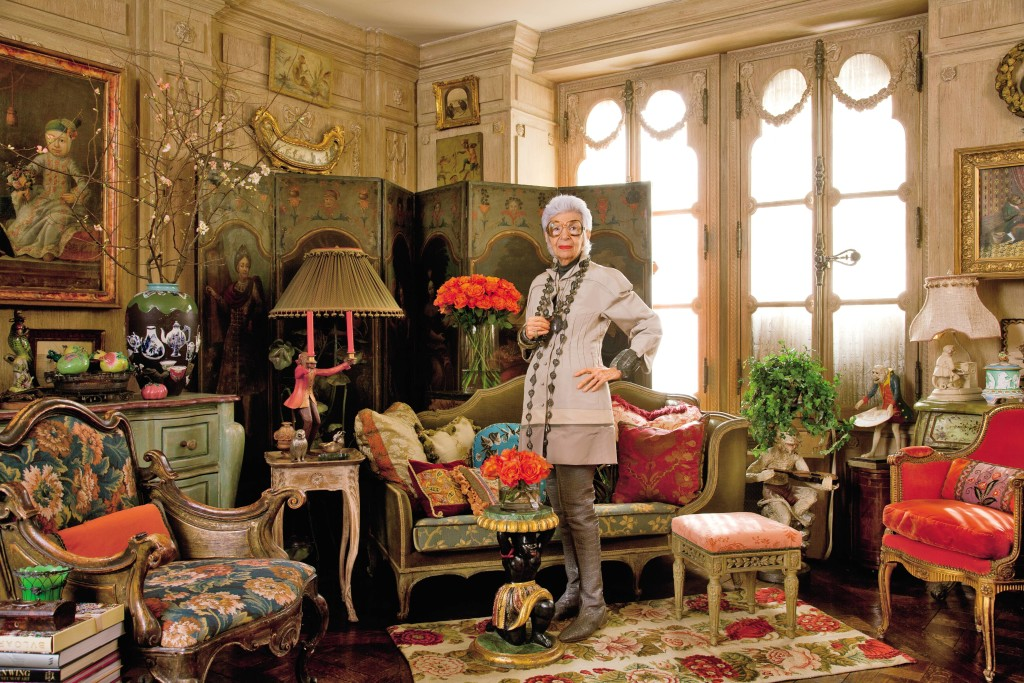 Iris Barrel Apfel—fashion muse, decorator, and cofounder of Old World Weavers—wearing Chado Ralph Rucci and jewelry of her own design in the New York City apartment she shares with her husband, Carl. The living room's bleached-oak boiserie is 18th-cen