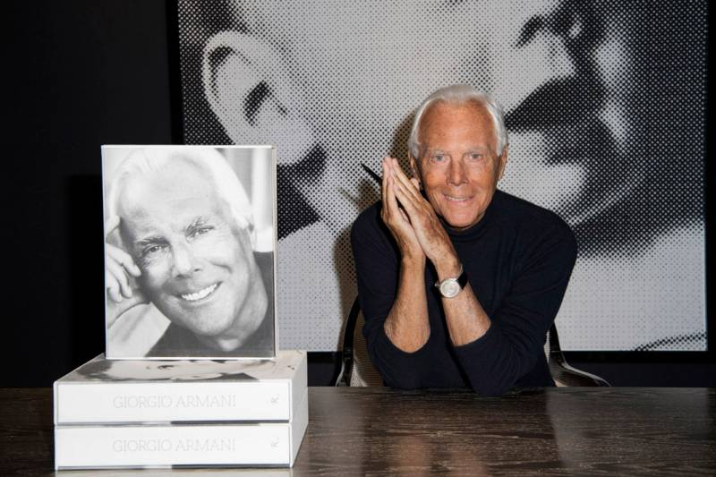 Armani accanto alle copie del suo libro autobiografico